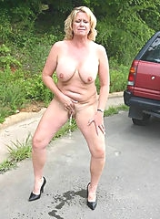 Busty mature is posing outdoors